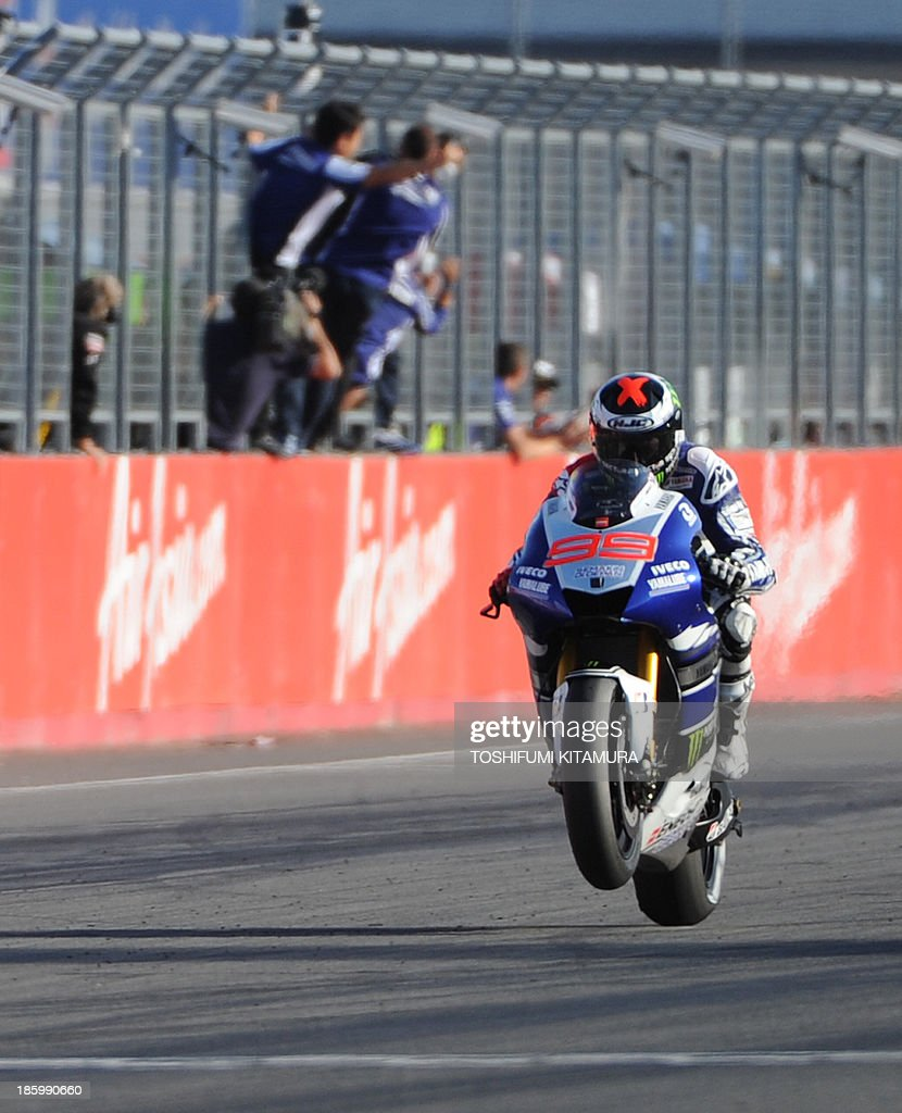 Yamaha Factory Racing rider Jorge Lorenzo of Spain (R) does a 'wheelie' across the finish line as he wins the MotoGP race of the Japanese Grand Prix at the Twin Ring Motegi circuit in Motegi on October 27, 2013. AFP PHOTO / TOSHIFUMI KITAMURA