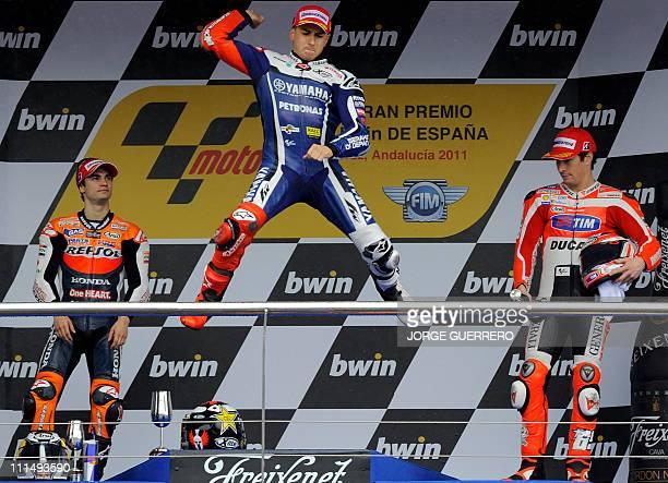 Yamaha Factory Racing's Spanish Jorge Lorenzo celebrates on the podium next to Repsol Honda Team's Spanish Dani Pedrosa and Ducati Team's US Nicky...