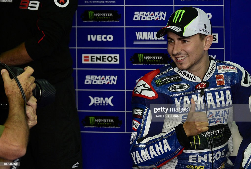 Yamaha Factory Racing's Spanish rider Jorge Lorenzo gives the thumbs up as he poses in the pits during the third MotoGP free practice session of the Aragon Grand Prix at the Motorland racetrack in Alcaniz on September 28, 2013.