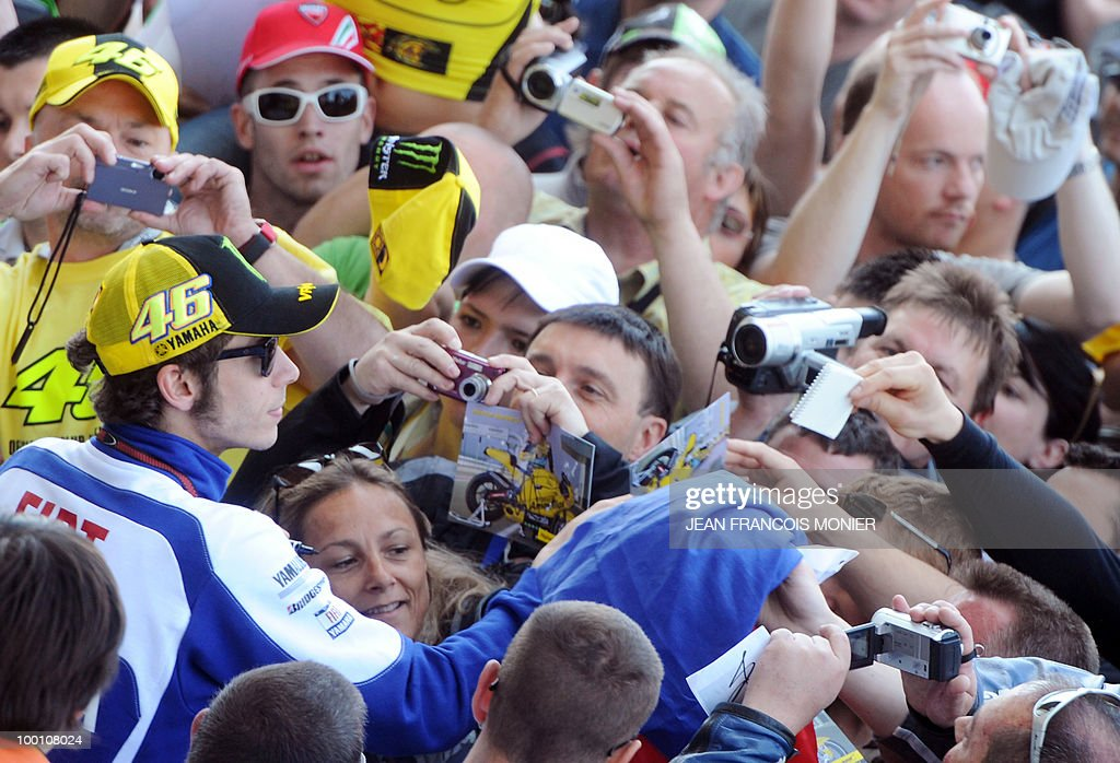 Yamaha Italian driver Valentino Rossi salutes signs autographs at Le Mans circuit on May 21, 2010, two days ahead of the MotoGP French Grand Prix.