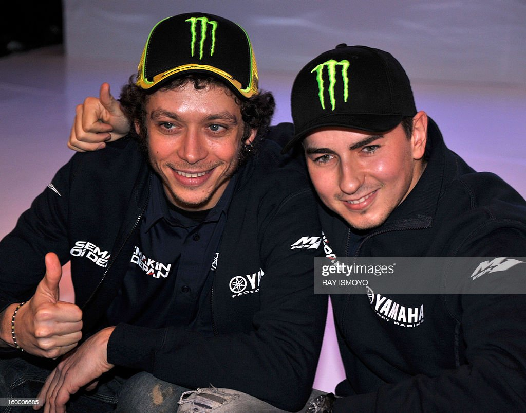 Yamaha Moto GP riders Valentino Rossi and Jorge Lorenzo (L and R) pose for photographers after a press conference in Jakarta on January 25, 2013. Rossi and Lorenzo were in Jakarta to promote Indonesian Yamaha's new slogan-logo, semakin di depan (getting ahead). AFP PHOTO / Bay ISMOYO