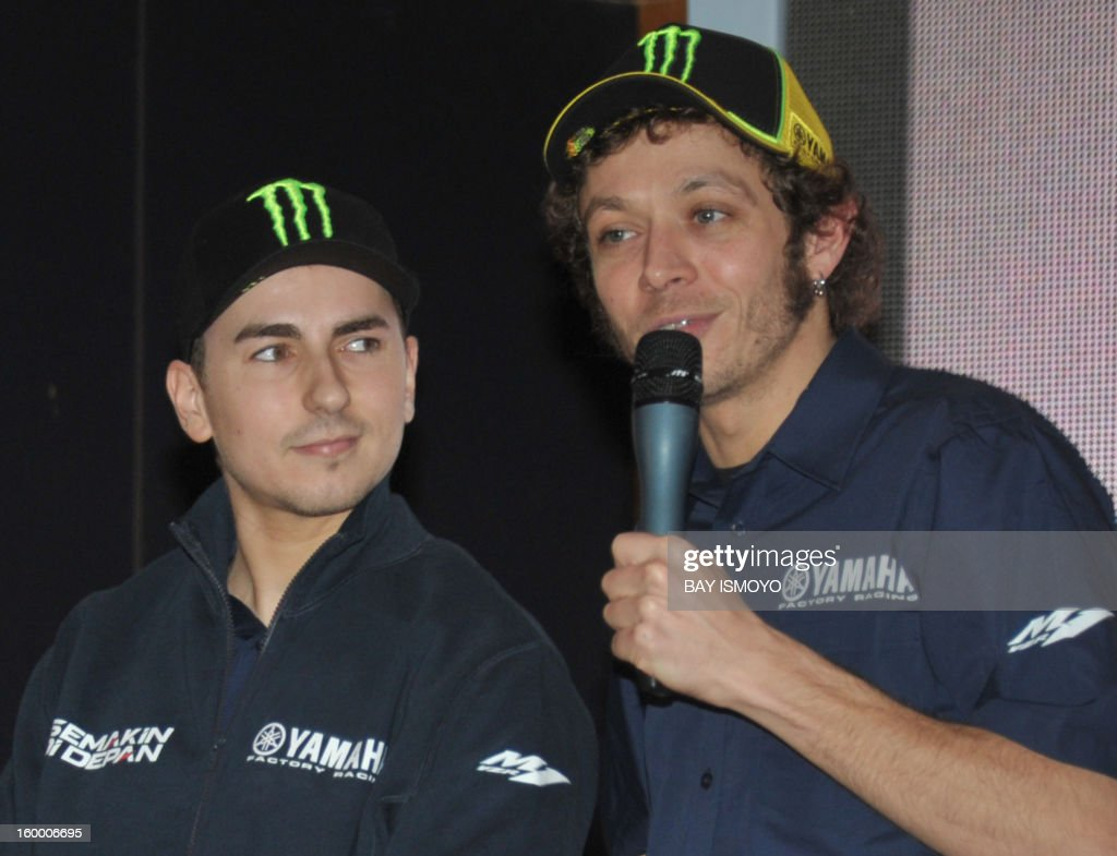 Yamaha Moto GP riders Valentino Rossi (R) answers journalists questions as his teammate Jorge Lorenzo (L) looks on during a press conference in Jakarta on January 25, 2013. Rossi and Lorenzo were in Jakarta to promote Indonesian Yamaha's new slogan-logo, semakin di depan (getting ahead). AFP PHOTO / Bay ISMOYO