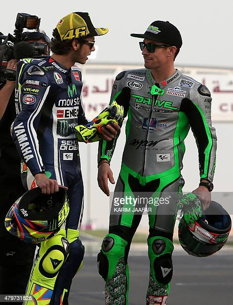 Yamaha MotoGP rider Valentino Rossi of Italy talks with Drive M7 Aspar Team's Nicky Hayden of the US before the start of the free practice session of...