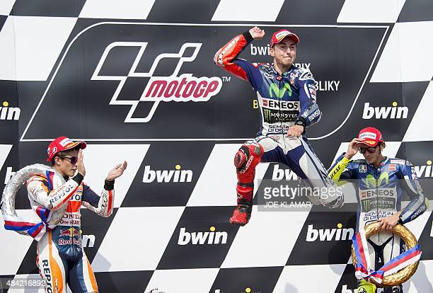 Yamaha MotoGP's Spanish rider Jorge Lorenzo jumps as he celebrate his victory with Repsol Honda Team's Spanish rider Marc Marquez and Yamaha MotoGP's...