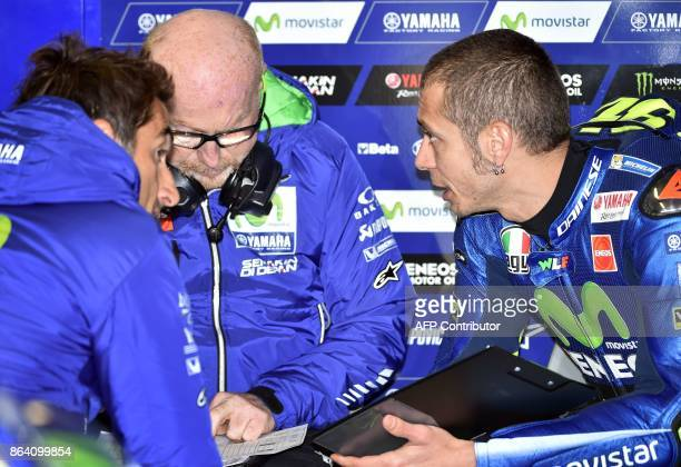 Yamaha rider Valentino Rossi of Italy consults with team members during the third practice session of the Australian MotoGP Grand Prix at Phillip...