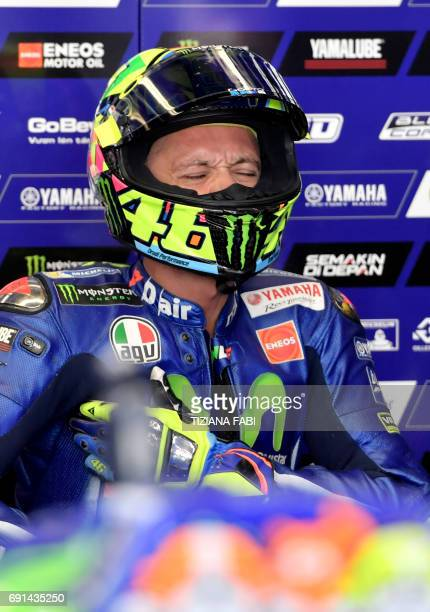 Yamaha team's Italian rider Valentino Rossi grimaces in the box during the Free Practice session ahead of the Italian motorcycling Grand Prix at the...