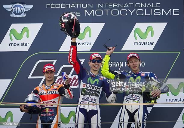 Yamaha Team's Spanish rider Jorge Lorenzo Repsol Honda's Spanish rider Dani Pedrosa and Yamaha Team's Italian rider Valentino Rossi celebrate on the...