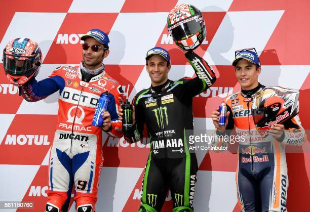 Yamaha Tech3 rider Johann Zarco of France celebrates his pole position while posing with second fastest Ducati rider Danilo Petrucci of Italy and...