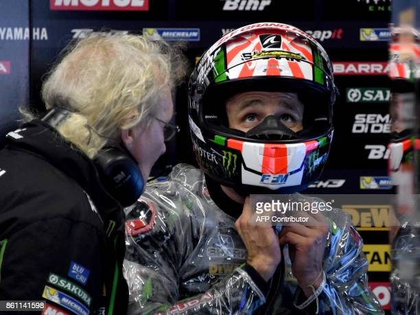 Yamaha Tech3 rider Johann Zarco of France listens to his mechanic Guy Coulon during the fourth practice round of the MotoGP Japanese Grand Prix at...