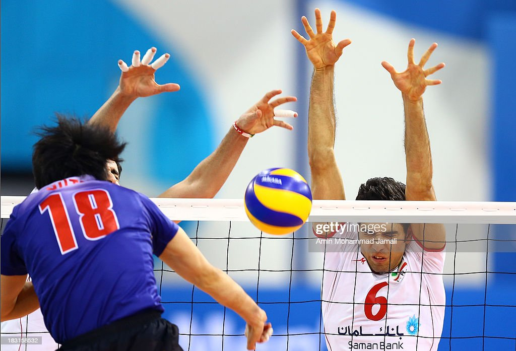 Yamamura Kota of Japan (L) and Seyed Mohammad Mousavi during 17th Asian Men's Volleyball Championship between Iran And Japan on October 5, 2013 in Dubai, United Arab Emirates.