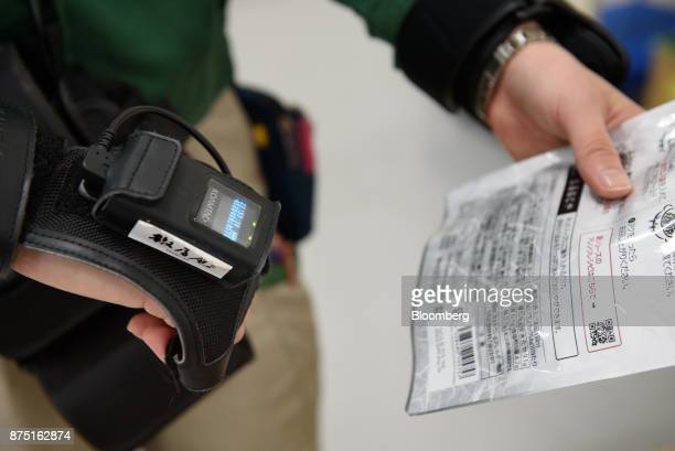A Yamato Logistics Co employee scans a product during a demonstration of inspection technologies at the Yamato Holdings Co Atsugi Gateway...