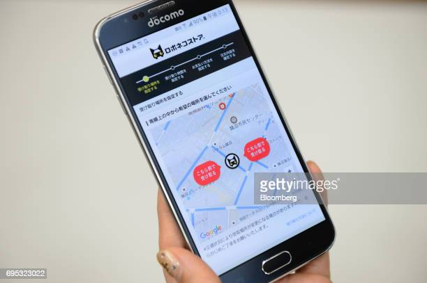 A Yamato Transport Co employee demonstrates a smartphone application for the Robonekoyamato autonomous van delivery service operated by Yamato...