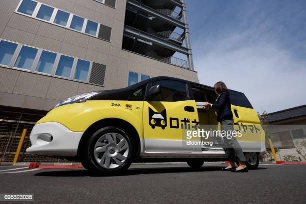 A Yamato Transport Co employee demonstrates the Robonekoyamato autonomous van delivery service operated by Yamato Transport Co and DeNA Co in...