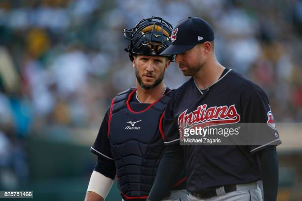 Yan Gomes and Corey Kluber of the Cleveland Indians stand on the field during the game against the Oakland Athletics at the Oakland Alameda Coliseum...