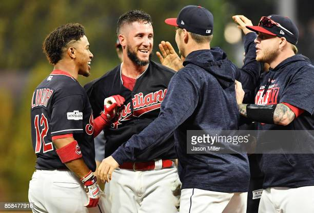 Yan Gomes of the Cleveland Indians celebrates with teammates after he hit a an RBI single scoring Austin Jackson to win the game 9 to 8 in the 13th...