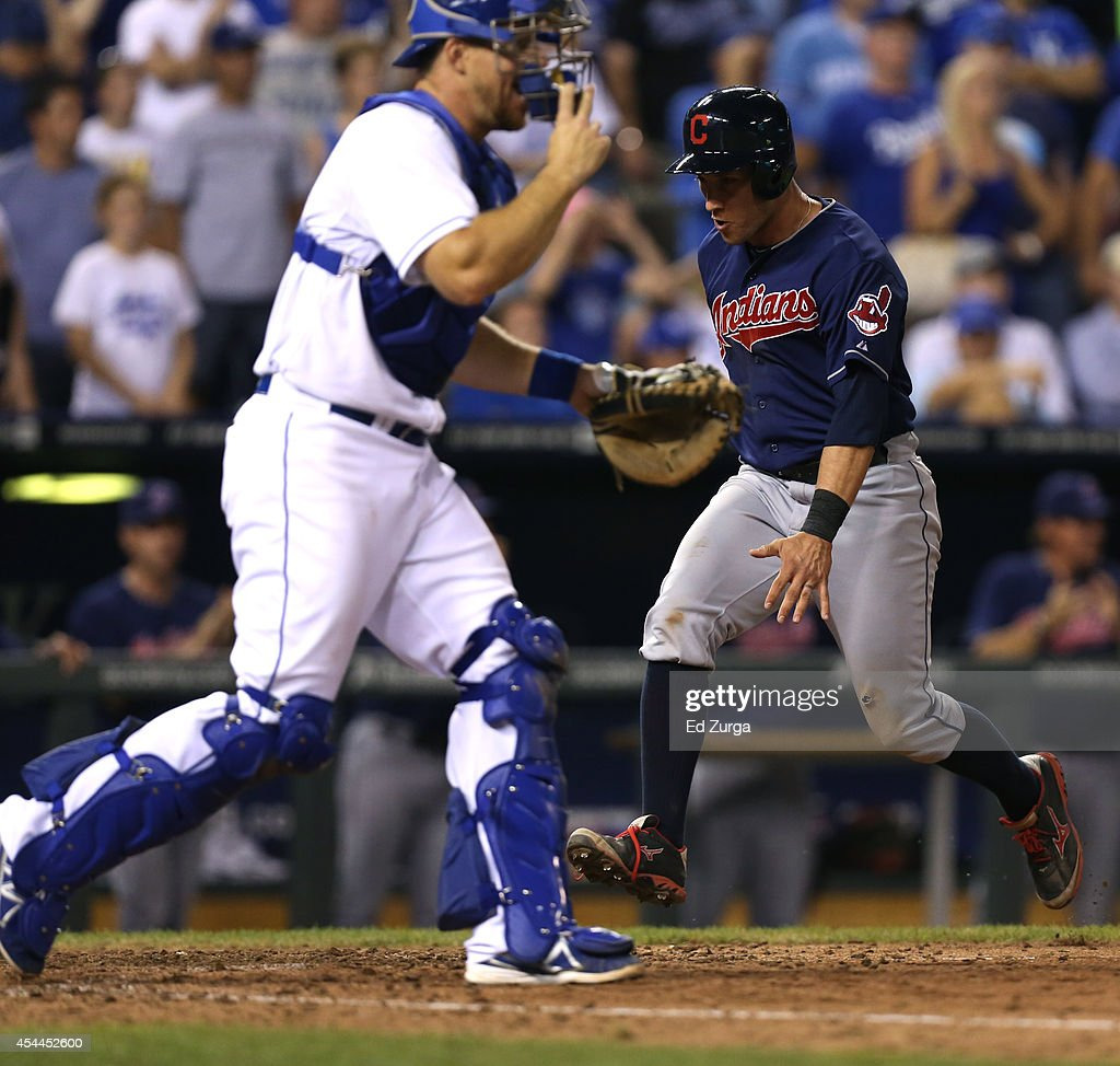 Yan Gomes of the Cleveland Indians crosses home to score past Erik Kratz of the Kansas City Royals as he scores on a Lonnie Chisenhall double in the...