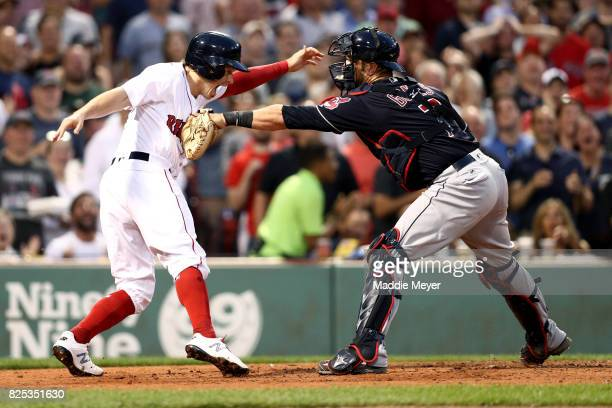Yan Gomes of the Cleveland Indians tags out Brock Holt of the Boston Red Sox at home during the second inning at Fenway Park on August 1 2017 in...