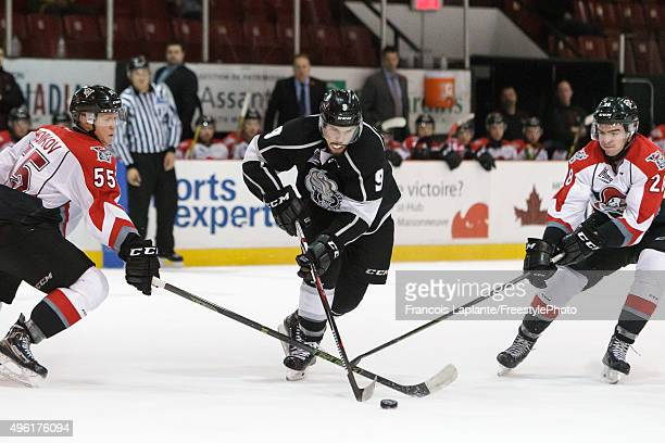 Yan Pavel Laplante of the Gatineau Olympiques controls the puck against Sergei Boikov and Frederic Aube of the Drummondville Voltigeurs on November 7...