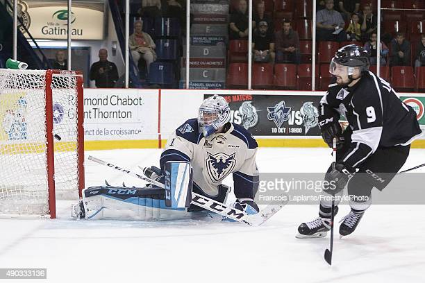 Yan Pavel Laplante of the Gatineau Olympiques puts the puck behind Evan Fitzpatrick of the Sherbrooke Phoenix in a breakaway on September 27 2015 at...