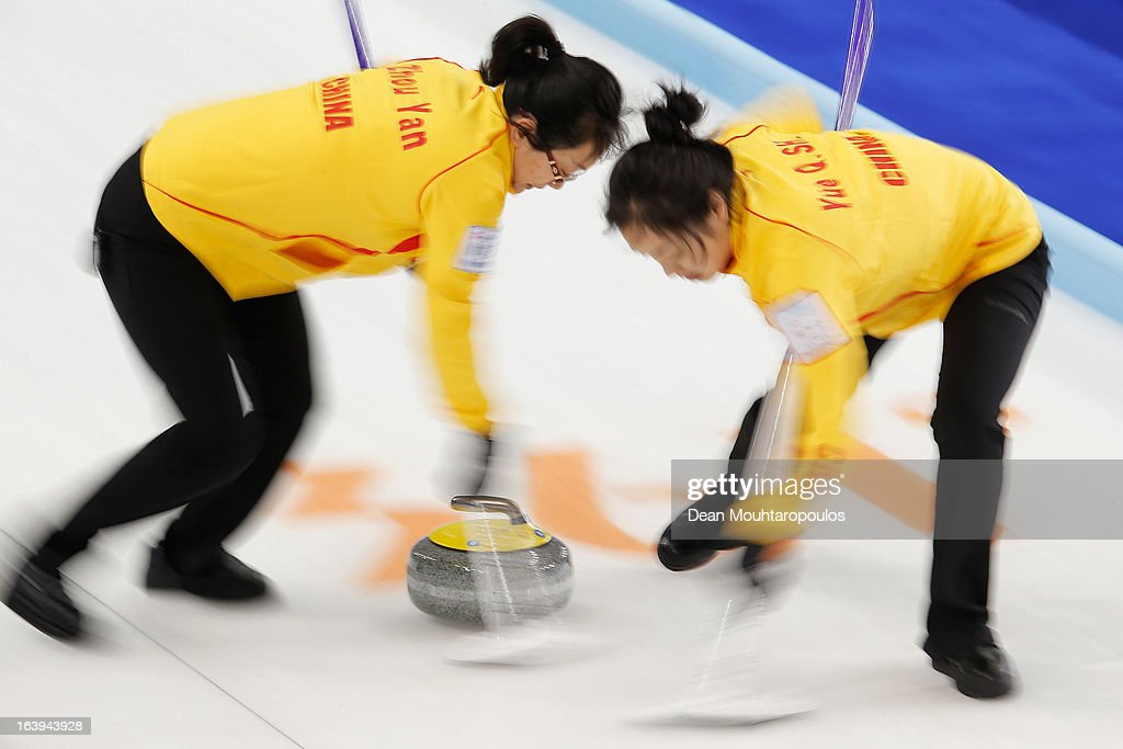 Yan Zhou (L) and Qingshuang Yue of China sweep in the match between China and Italy during Day 3 of the Titlis Glacier Mountain World Women's Curling Championship at the Volvo Sports Centre on March 18, 2013 in Riga, Latvia.