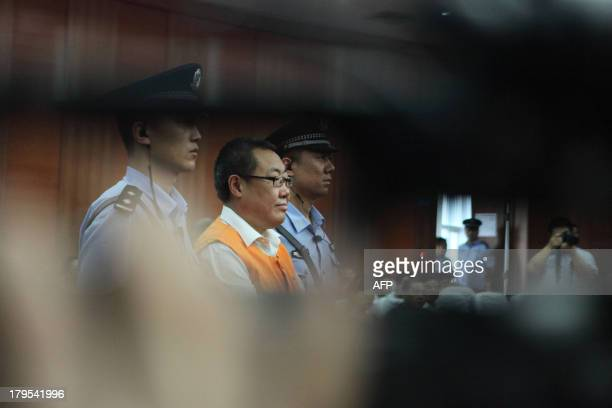 Yang Dacai a Chinese official branded 'Brother Watch' because of his expensive taste in timepieces stands in the courtroom in the Intermediate...