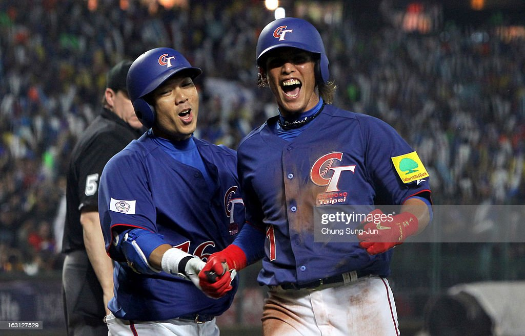 Yang Dai-Kang #1 of Chinese Taipei celebrates with Chou Szu-Chi # 16 in the third inning during the World Baseball Classic First Round Group B match between Chinese Taipei and South Korea at Intercontinental Baseball Stadium on March 5, 2013 in Taichung, Taiwan.