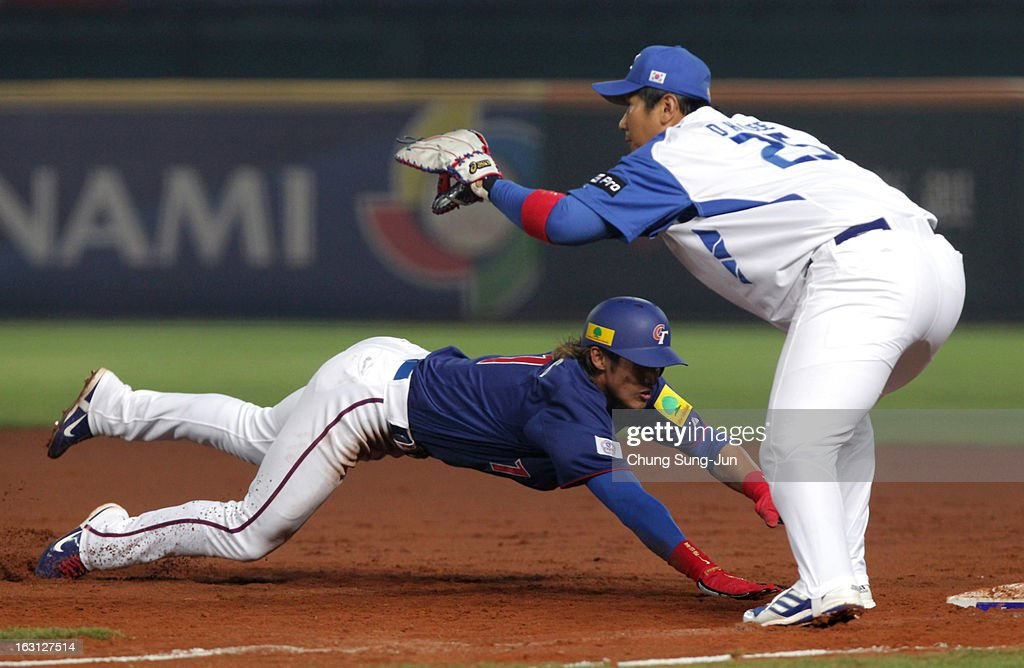 Yang Dai-Kang of Chinese Taipei slides back to fiirst base as Lee Dae-Ho of South Korea tags in the third inning during the World Baseball Classic First Round Group B match between Chinese Taipei and South Korea at Intercontinental Baseball Stadium on March 5, 2013 in Taichung, Taiwan.