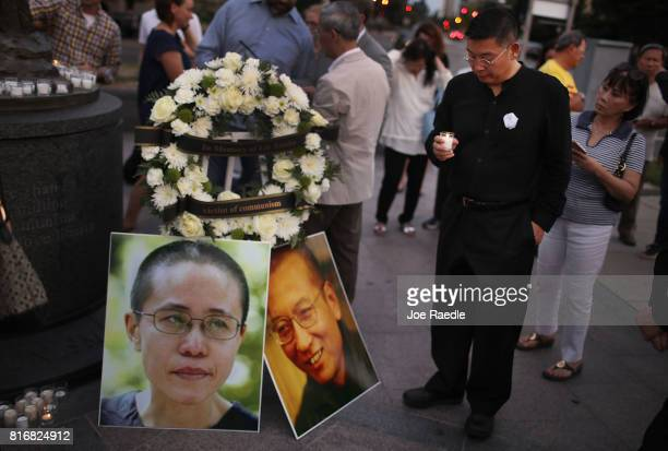 Yang Jianli holds a candle during a vigil in memory of Chinese Nobel Peace Prize laureate Liu Xiaobo on July 17 2017 in Washington DC Liu died of...