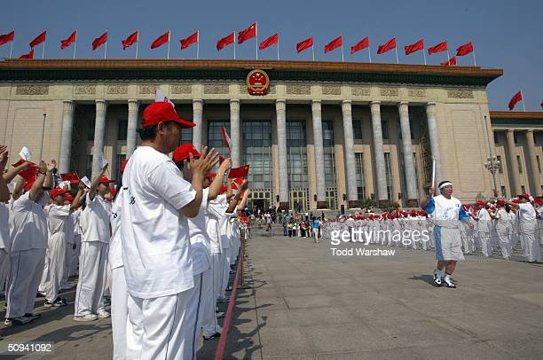 Yang Ling carries the flame outside The Great Hall of the People during Day 6 of the Athens 2004 Olympic Torch Relay on June 9 2004 in Beijing China...