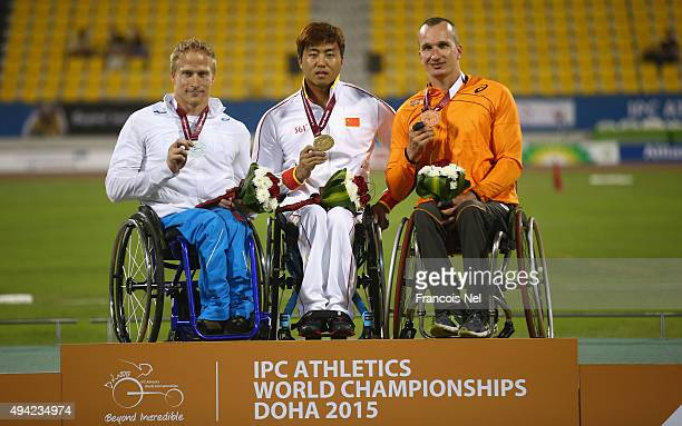 Yang Liu of China poses with his gold Leo Tahti of Finland silver Kenny van Weeghel of Holland bronze after the men's 100m T54 during the Evening...