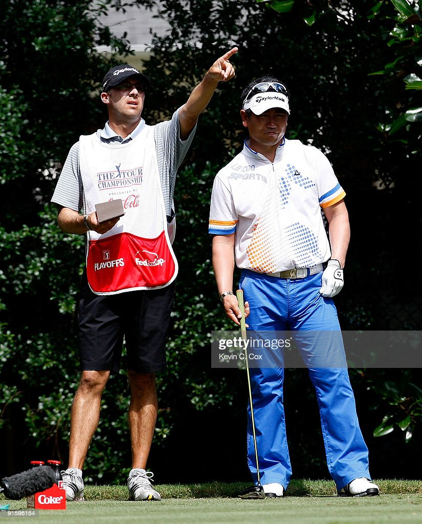 Y.E. Yang of Korea (R) and caddie A.J. Montecinos look on during the first round of THE TOUR Championship presented by Coca-Cola, the final event of the PGA TOUR Playoffs for the FedExCup, at East Lake Golf Club on September 24, 2009 in Atlanta, Georgia.