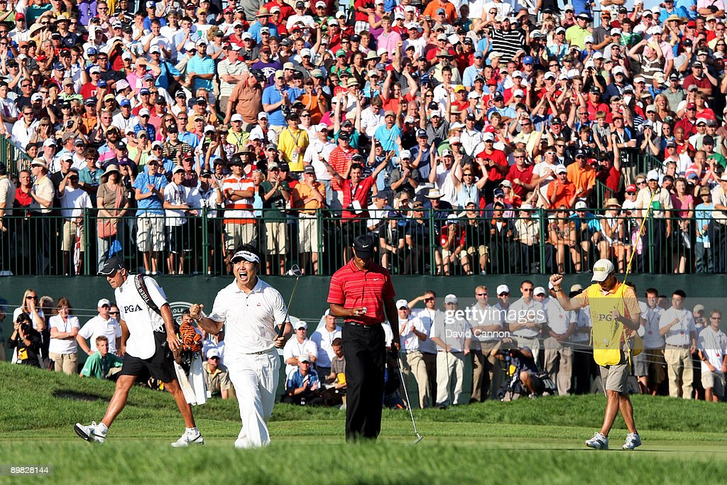 E Yang of South Korea celebrates a birdie putt on the 18th green alongside Tiger Woods during the final round of the 91st PGA Championship at...