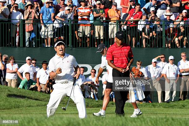 YE Yang of South Korea celebrates a birdie putt on the 18th green alongside Tiger Woods during the final round of the 91st PGA Championship at...