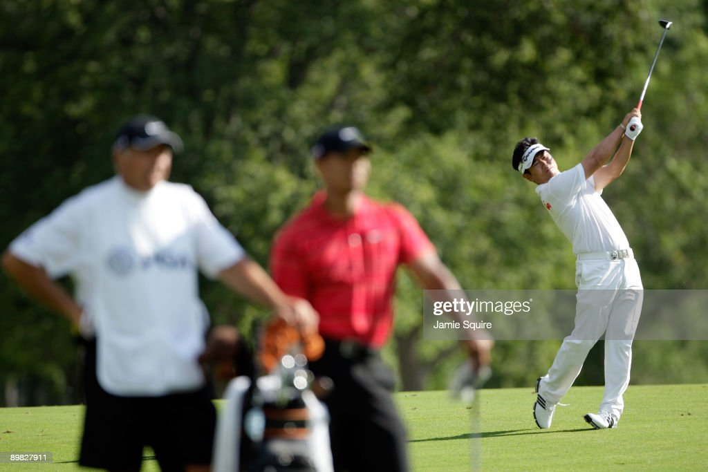 E Yang of South Korea hits a shot on the 15th hole as Tiger Woods and his caddie Steve Williams look on during the final round of the 91st PGA...