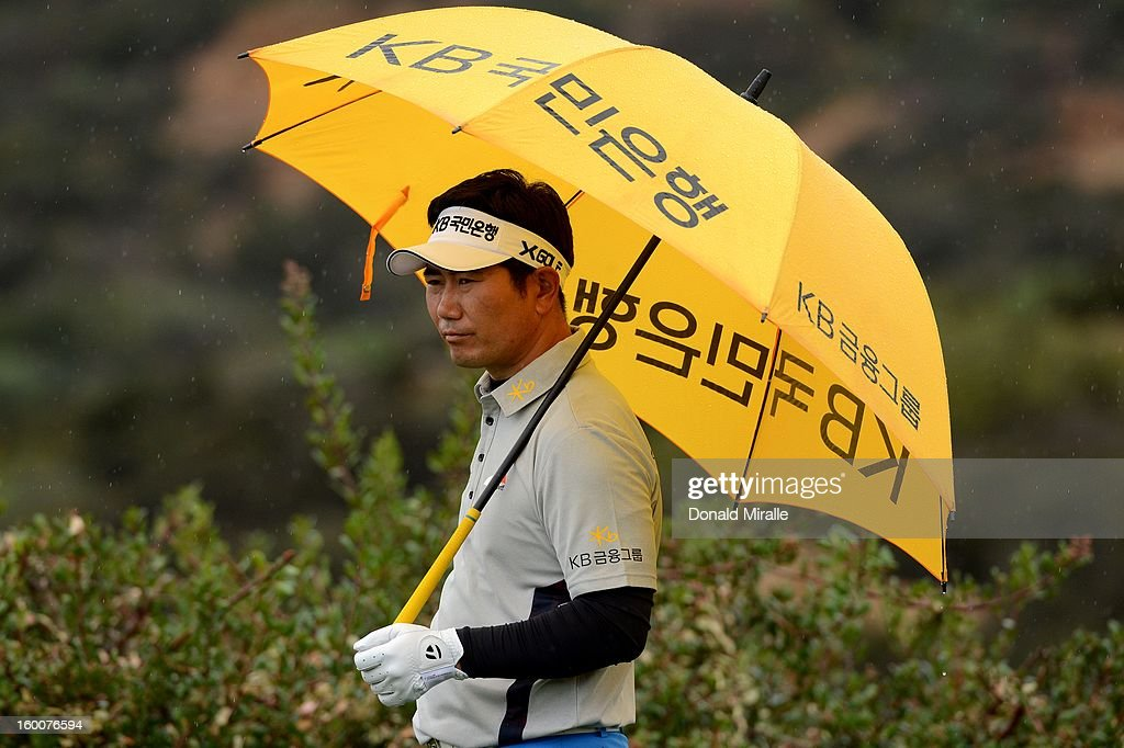 Y.E. Yang of South Korea looks onto the green after losing his ball in the bushes during the first round at the Farmers Insurance Open at Torrey Pines North Golf Course on January 25, 2013 in La Jolla, California.