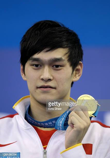 Yang Sun of China poses with the gold medal after winning in a new world record the Men's 1500m Freestyle Final during Day Sixteen of the 14th FINA...