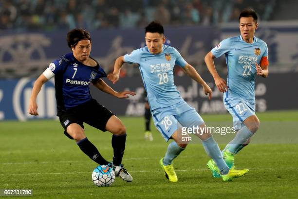 Yang Xiaotian of Jiangsu FC fights for the ball with Yasuhito Endo of Japan's Gamba Osaka during their AFC Champions League group stage football...