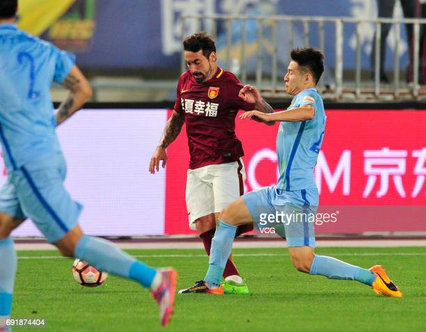 Yang Xiaotian of Jiangsu Suning and Ezequiel Lavezzi of Hebei China Fortune FC compete for the ball during the 12th round match of 2017 Chinese...
