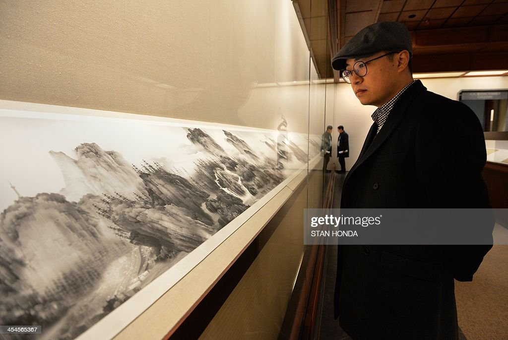 Yang Yongliang looks at his 'View of Tide,' an inkjet print of a composite photograph, on display in the exhibition 'Ink Art: Past as Present in Contemporary China' at the Metropolitan Museum of Art on December 9, 2013 in New York. A major exhibition of 70 pieces of art by 35 contemporary artists born in China goes on view to the public on December 11. AFP PHOTO/Stan HONDA ++RESTRICTED