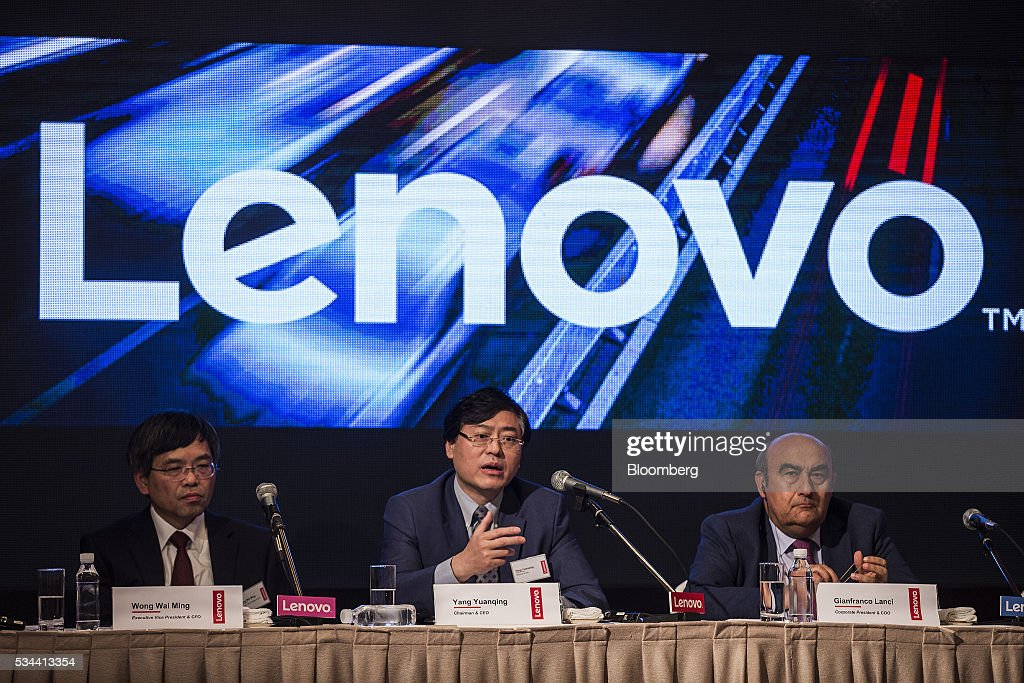 Yang Yuanqing, chairman and chief executive officer of Lenovo Group Ltd., center, speaks as Wong Wai Ming, executive vice president and chief financial officer of Lenovo Group Ltd., left, and Gianfranco Lanci, corporate president and chief operating officer of Lenovo Group Ltd., listen during a news conference in Hong Kong, China, on Thursday, May 26, 2016. Lenovo posted fourth-quarter profit that missed analysts' estimates as it struggles to revive the Motorola smartphone brand and the personal computer market continues to slide. Photographer: Justin Chin/Bloomberg via Getty Images