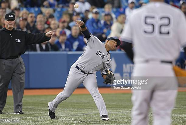 Yangervis Solarte of the New York Yankees cannot throw out the baserunner in the first inning during MLB game action as Maicer Izturis of the Toronto...