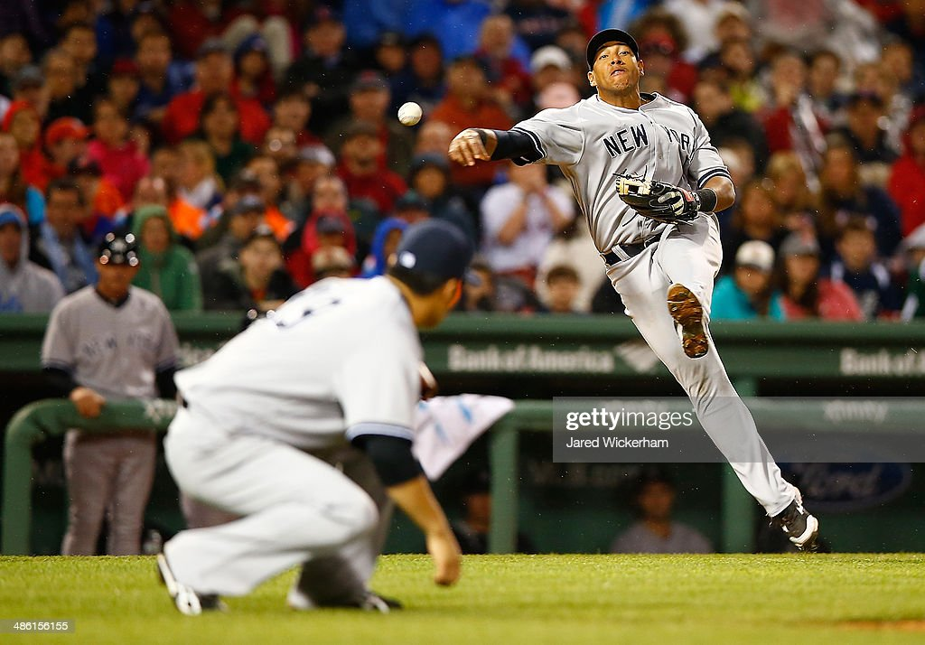 Yangervis Solarte #26 of the New York Yankees throws to first base over his teammate Masahiro Tanaka #19 against the Boston Red Sox during the game at Fenway Park on April 22, 2014 in Boston, Massachusetts.