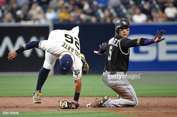 Yangervis Solarte of the San Diego Padres can't get the force out at second base as Carlos Gonzalez of the Colorado Rockies signals safe during the...