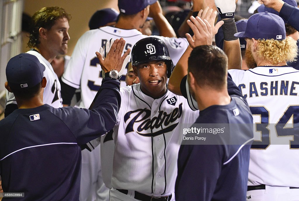 Yangervis Solarte #27 of the San Diego Padres, center, is congratulated in the dugout after hitting a two run home run during the seventh inning of a baseball game against the Colorado Rockies at Petco Park August, 11, 2014 in San Diego, California.