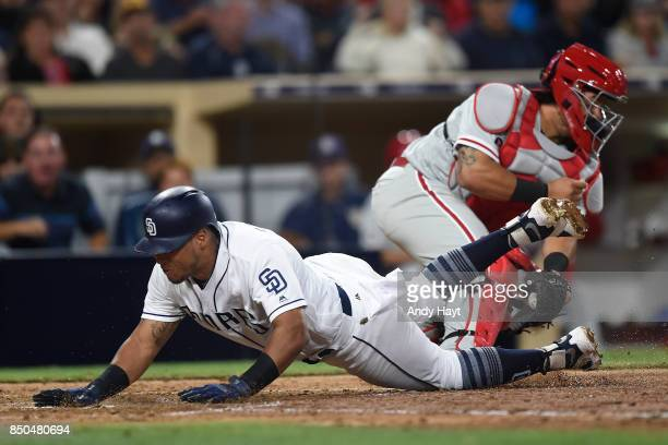 Yangervis Solarte of the San Diego Padres dives as scores past the the tag of Jorge Alfaro of the Philadelphia Phillies during the fifth inning of a...