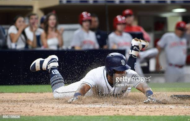 Yangervis Solarte of the San Diego Padres slides as he scores ahead of the tag of Devin Mesoraco of the Cincinnati Reds during the fifth inning of a...