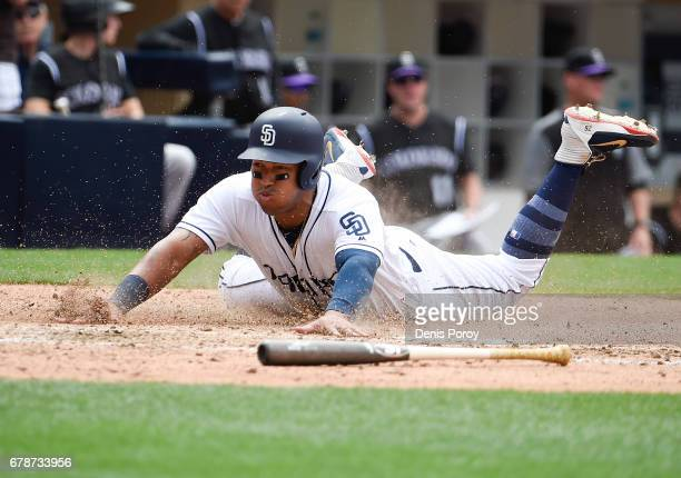 Yangervis Solarte of the San Diego Padres slides as he scores during the seventh inning of a baseball game against the Colorado Rockies at PETCO Park...