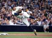 Yangervis Solarte of the San Diego Padres throws to first base as he tries to to get the out on Austin Romine of the New York Yankees during the...
