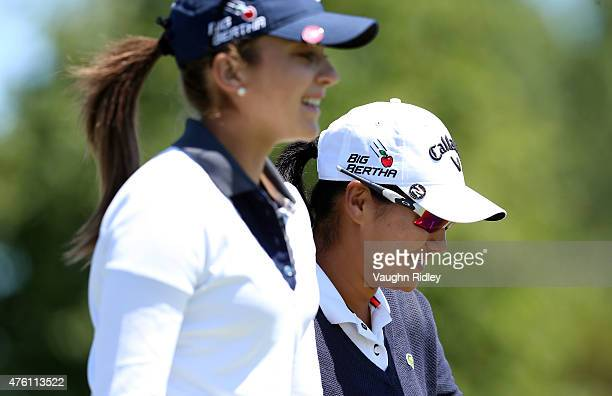 Yani Tseng of Chinese Taipei and Kim Kaufman of the USA chat as they walk up the fairway of the 1st hole during the third round of the Manulife LPGA...