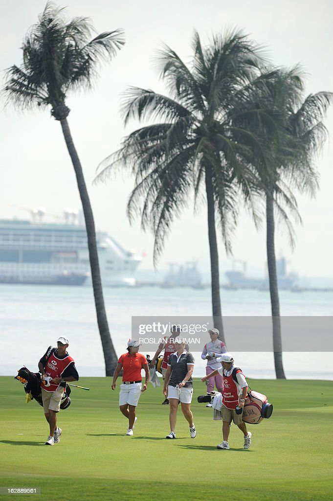 Yani Tseng of Taiwan (2nd L at front), Brittany Lincicome of the US (2nd R at front) and Amy Yang of South Korean (R at rear) walk along the fairway during round two of the HSBC Women's Champions LPGA golf tournament at the Serapong Course in Singapore on March 1, 2013. The 1.4 million USD tournament takes place from February 28 to March 3. AFP PHOTO / ROSLAN RAHMAN